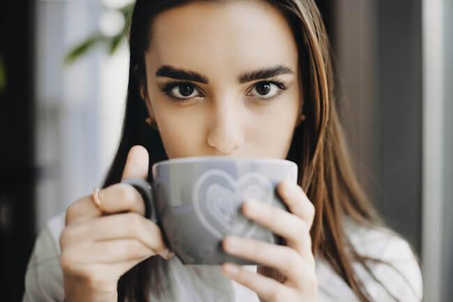 ハートのマグカップで飲み物を飲む女性