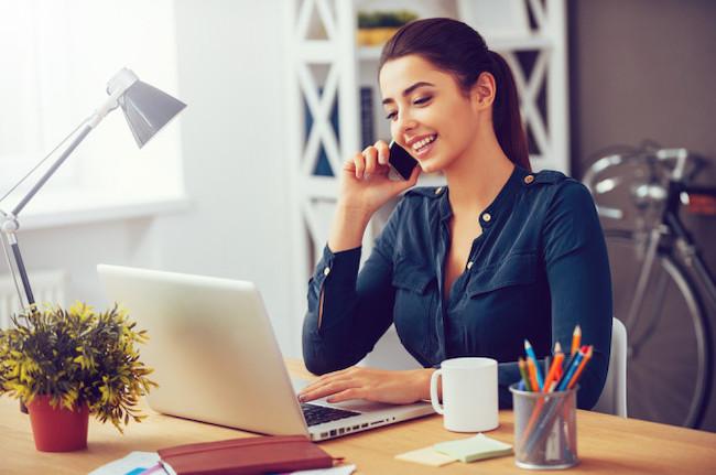 パソコンを見ながらスマホで電話する女性 在宅勤務