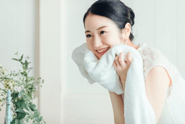 洗顔後タオルで顔を抑える女性
