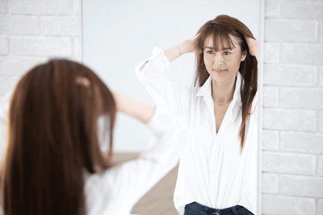 鏡を見ながら頭皮マッサージする女性