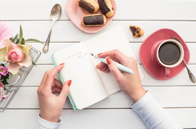 ノートに文字を書く女性の手 コーヒー 花 お菓子